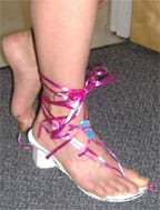 A photograph shows a girl's foot in a strappy heeled shoe made of foam core and ribbons.