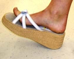 A photograph shows the bare foot of a person wearing a white-strapped sandal with a two-inch thick hemp platform sole.