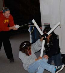 A photograph shows three students launching a t-shirt from a big y-shaped device made of PVC piping; it looks like a big slingshot.