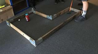 A photograph shows a wooden frame placed on a carpeted floor. The frame edges are made of 2 x 4-inch wood with galvanized metal corner joints as connectors and enclose an L-shaped interior space. A student has just used a golf putter to hit a golf ball from one end of the L shape towards a water bottle (which serves as the hole/goal) in the far side of the L shape.
