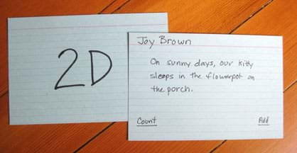 "A photograph shows two index cards, one with ""2D"" written on it and the other with: Joy Brown; On sunny days, our kitty sleeps in the flowerpot on the porch; Count; Add."