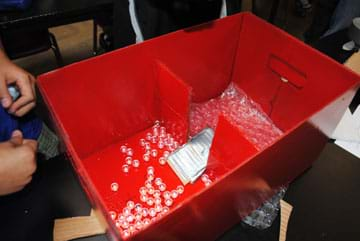 Photo shows a red box with an inner cardboard wall dividing it into two sections. The middle portion of the inner wall contains a one-way valve made in the form of a cardboard and duct tape ramp. Loose marbles are scattered around the floor of both box sections.