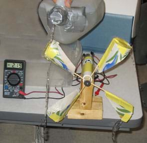 Photo shows a hand holding a plastic gallon jug of water with the spout taped to restrict water flow and pouring water over paper cup turbine blades. A nearby multimeter reads 2.19.