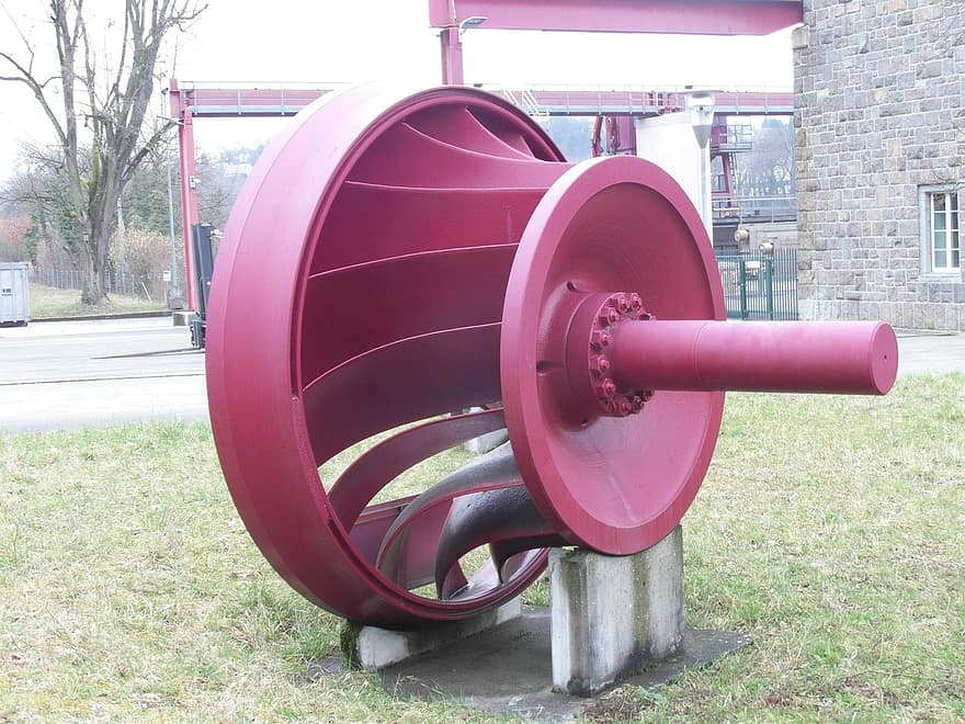 A photo of a large red turbine shaft with curved blades attached like spokes from a hub.