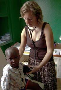 A female adult measures the heart rate of a child.