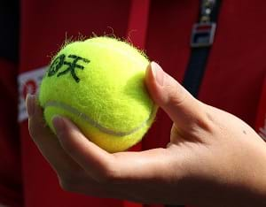An individual holding a tennis ball in their hand.