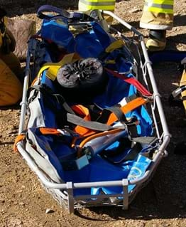 An photograph shows an empty rescue litter up close. Shown is a nonsolid device with a flat surface, similar to a flattened, shallow bowl. Railed sides prevent a person from sliding out of the litter when strapped in (colored security straps shown).