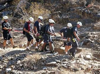 A photograh shows seven people assisting with transporting an injured person down the rocky slope of a mountain. The injured person is on flat surface (similar to a long board) with railed sides; the carrying surface is attached to one large treaded tire, allowing for easier movement over the rough terrain.