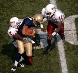 Two football players tackle another football player while wearing padded uniforms on the field during a game.
