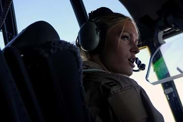 A photograph shows a female pilot in the cockpit of an aircraft wearing headphones that include a microphone placed near her mouth as she communicates on the radio.