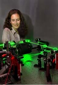 Photo shows a girl standing by green glowing laser beams.