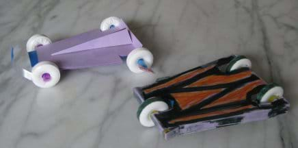 A photo shows two little race cars made from round white candies (for wheels), plastic drinking straws (for axles) and card stock (for cut and taped body chassis shapes).
