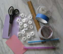 A photo shows scissors, tape, ruler, straws, lifesaver-shaped white candies and index cards in a pile on a tabletop.