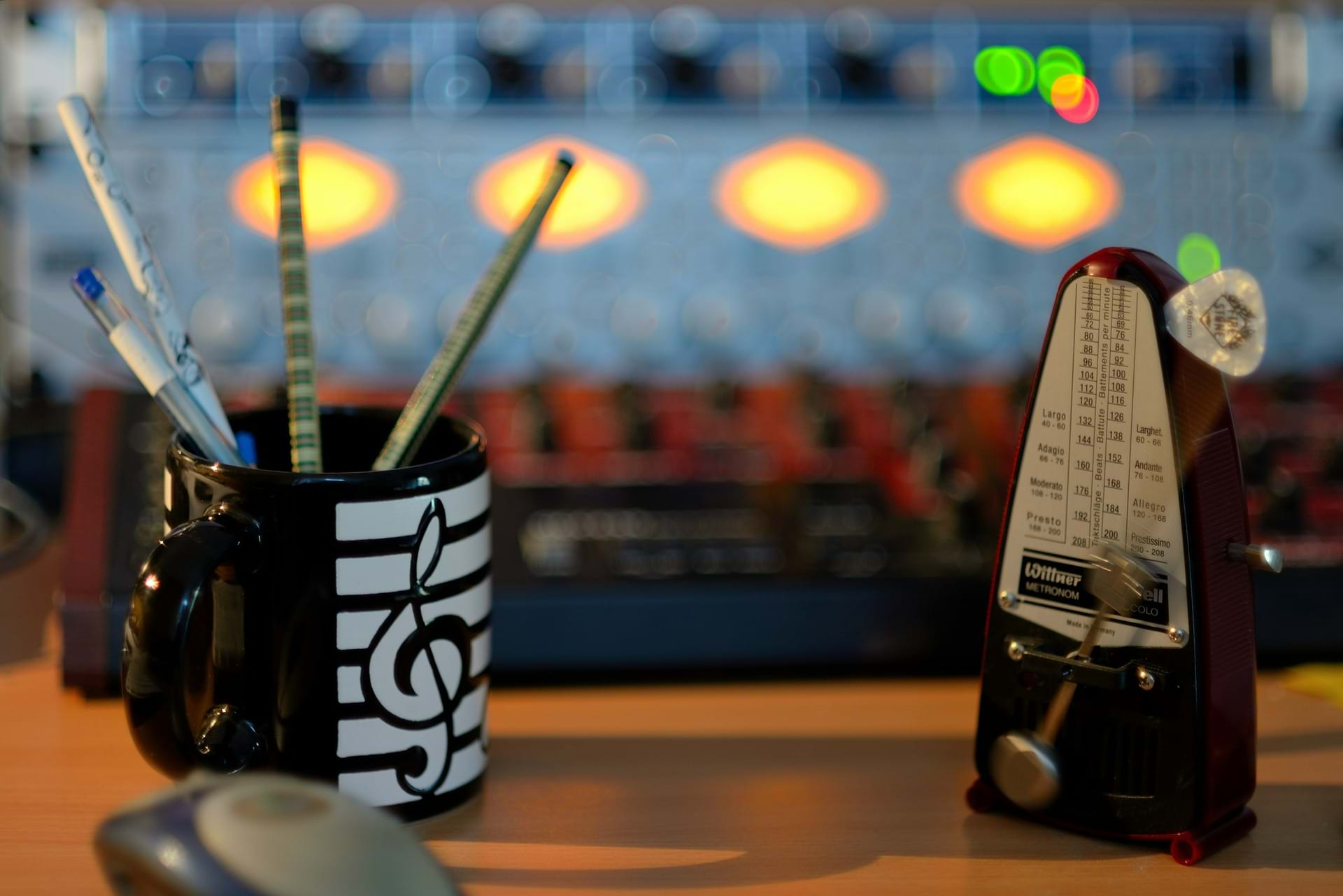 A metronome with a cup with a music note with pens