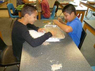 Photo shows two students seated at a table, picking beans out of a bin of sand.