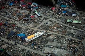 The aftermath of a 9.0 earthquake and tsunami in Japan: A large ferry boat rests inland around destroyed houses.