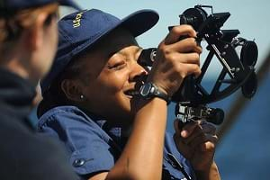 A Coast Guard Academy Cadet onboard the USCGC Eagle uses a sextant to take a sun line.