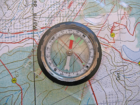 A compass resting on top of a map.