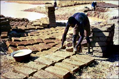 Photo shows two men making adobe bricks and laying them out in the sun to dry.