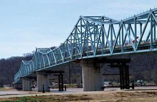 A photograph shows the Milton-Madison Bridge, a truss bridge that crosses a river in Indiana. The metal truss bridge is painted blue and rests on concrete piers.