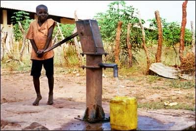 A boy pushes down on a lever as he pumps water into a yellow container.