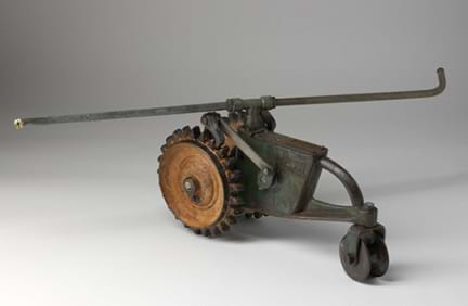 Photo shows a steel garden sprinkler shaped like a tractor with one small front wheel and two larger, treaded back wheels.
