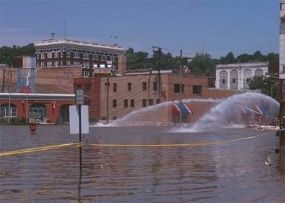 A photograph shows a flooded downtown area with many one to four-story brick buildings. The flood waters reach the bottom of a stop sign. Sprays of water, move water to a different location.