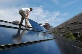 Two men standing on an angled roof lay a shiny blue-black panel on its surface.