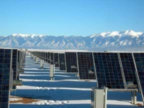 Photo shows endless rows of angled photovoltaic panels mounted on a snow-covered field with a background of snowcapped mountains and blue skies.