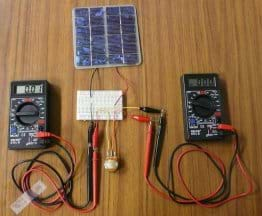 Photo shows two multimeters and a potentiometer on a table hooked up with wires and alligator clips to a circuit board wired to a mini PV panel. Circuit board also wired to round device.