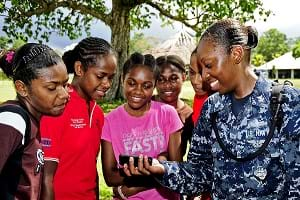 A US Navy officer shows five teenage girls a music video on her cellphone.