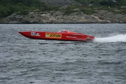 A photo shows a red speed boat skimming very fast across the water.