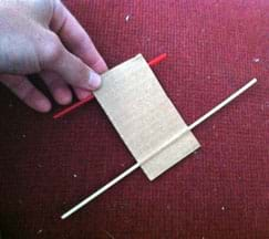 A photograph shows a hand holding a 3 x 5-inch piece of corrugated cardboard with a wooden skewer pushed through the short side via a channel between the cardboard paper layers at one end and a red plastic coffee stirrer inserted through a similar paper channel at the other end. This shows how to place the stirrer axles for the sail car base.