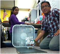 A photograph in a classroom shows a boy positioning a toy-sized sail car in front of a box fan while a girl operates the fan control switch.