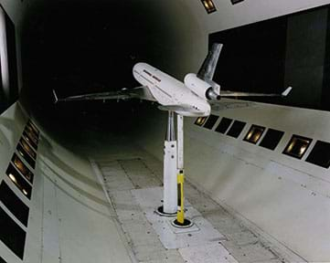 A photograph shows a small-sized a passenger airplane mounted from below inside a wind tunnel.