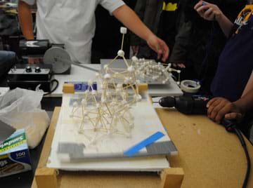 On a tabletop surrounded by students, two framework structures made of toothpicks and mini marshmallows jiggle on moving platforms; one structure has collapsed.