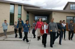 Photo shows nine high school students and two instructors walking out the front door of a building.