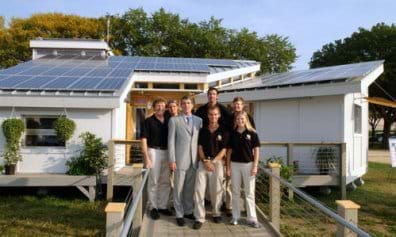A photo shows a one-story house in which the entire roof surface is angled in one direction and entirely covered with blue solar panels. Five engineering students, their professor and a congressman stand at the entry.