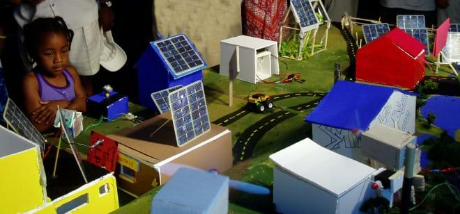 Photo shows a young girl gazing at a table covered with a miniature town composed of an assortment of model buildings and streets, with plenty of small solar panels in evidence.