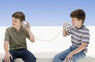 Two young boys using string and cups to model a string telephone.