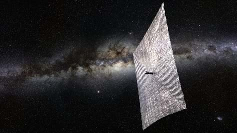 A reflective square sail pushes a cube satellite through the blackness of space as light reflects off of the sail's silvery surface.