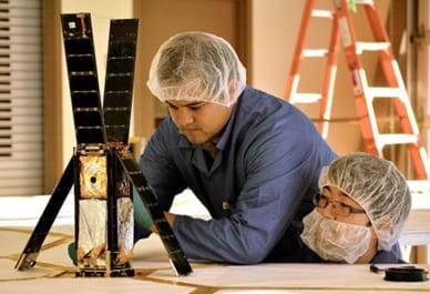 Two men wearing hair and beard nets examine a device on a table. Four solar panel-covered sides of the tall rectangular object (shoe-box sized) are flipped up or away to reveal the inside volume of the satellite cube, which contains a folded-up silver and gold fabric.
