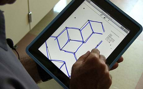 A photograph shows a hand sketching an isometric drawing of an object on a handheld tablet computer.