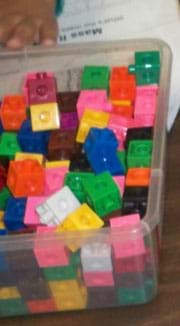 A photograph shows a clear plastic tub filled with assorted same-size snap cube blocks in many colors.