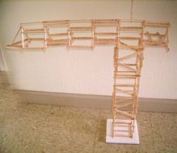 About 100 Popsicle sticks glued end-to-end to create a truss-like tower with a horizontal top structure longer on one side than the other.
