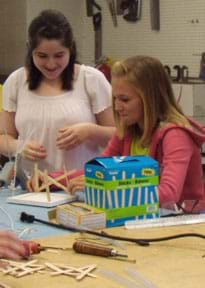 Photo shows two teenage girls gluing Popsicle sticks in a crossed pattern rising from a square foam core board base.