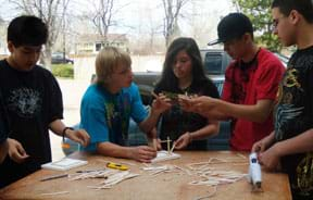 Photo shows five students around a work table, discussing the arrangement for how to glue Popsicle sticks rising up from their square base.
