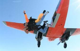 Two Skydivers jump out of an orange airplane.