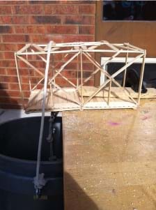 Photo shows a Popsicle stick model truss positioned with half of it extending over the edge of a table. The truss is secured to the table using a clamp and a piece of wood. A bucket is hung from the cantilevered end by a rope.