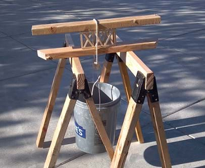 Photo shows a truss sandwiched between two 2x4s, and the sandwich is placed across a set of saw horses. The bucket is hung below the truss by looping the rope over the sandwiched truss.